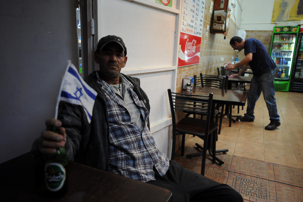 Ofakim, Israel - November 18, 2012: An Israeli man holds Israeli flag on a bottle of beer in a local restaurant short after a rocket attack, fired from Gaza Strip, caused the injury of four civilians, at the fifth day of Operation Pillar of Defense. Photo by Gili Yaari  - Israel Photojournalist