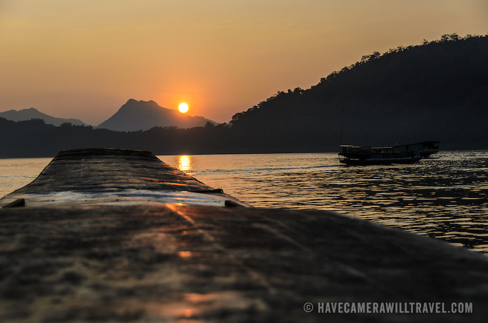Just before the sun disappears behind a mountain on the horizon on the Mekong River near Luang Prabang, Laos. In the foreground is the roof of a wooden sampan pointed towards the sun.