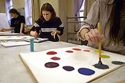 16248Art Students Painting and Seigfred Gallery Show Strange Affinities: j Hanson..Sophomore, Kathryn Locker, center, works on her color wheel in a art class in Seigfried Hall. The students started with primary colors and then had to create the secondary colors of the wheel.