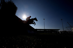 A runner in The 888Sport Pendil Novices' Steeple Chase clears an early fence at Kempton Park Racecourse.