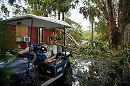 Robert Market, 82, sits in a golf cart in his front yard filled with fallen trees, flood waters, and debris, following Hurricane Irma, near Jerome, Florida, U.S., September 12, 2017. REUTERS/Bryan Woolston