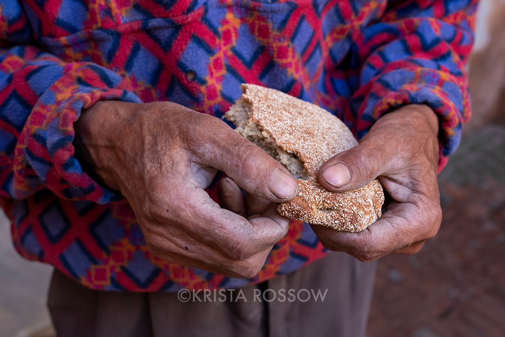 A man holds fresh bread in the Medina of Marrakech, Morocco.