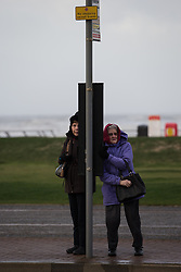 "© Licensed to London News Pictures . 10/12/2014 . Blackpool , UK . Two women shelter from high winds at a bus stop on Blackpool Promenade . An explosive cyclogenesis - a fast developing storm in which air pressure falls rapidly - known as a "" weather bomb "" - hits the North of England , bringing storms to the region . Photo credit : Joel Goodman/LNP"