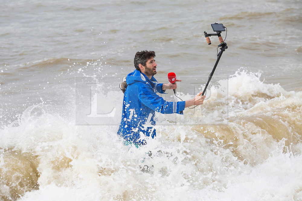 © Licensed to London News Pictures. 31/03/2018. Brighton, UK. A man is seen filming himself in the sea in Brighton and Hove as powerful waves hitting the seafront during the Easter Bank Holiday weekend. Photo credit: Hugo Michiels/LNP
