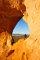 "A woman stands looking out on the landscape in the ""Looking Glass"" arch on Looking Glass Rock in Southeast Utah, USA."