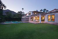 Lawn and swimming pool with lit exterior of Palm Springs home exterior