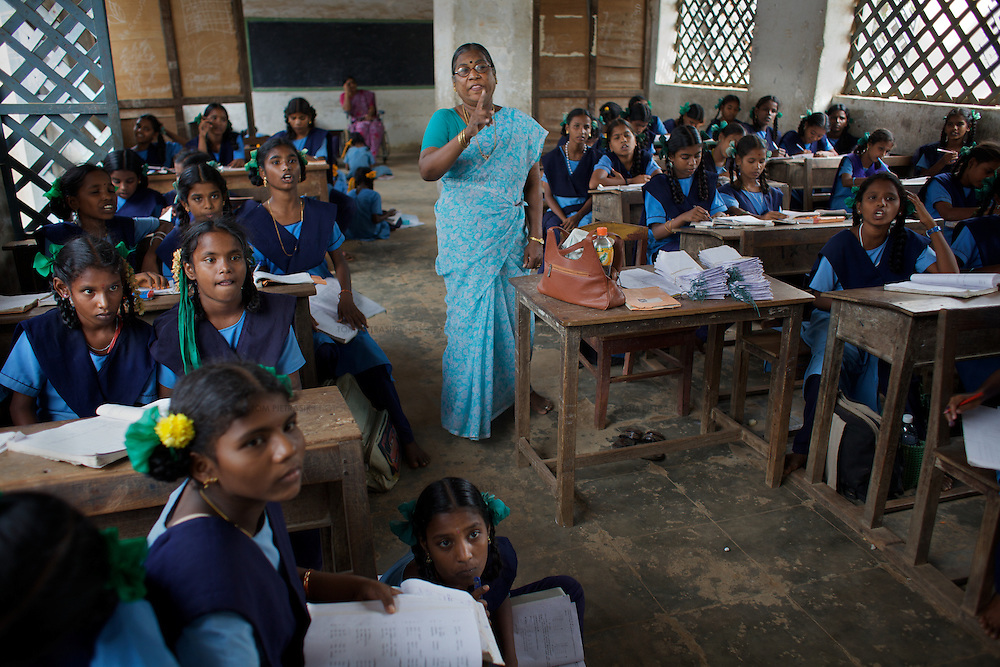 "Staff and pupils at the Government Girls High School, Venugopalapuram, Cuddalore...Cuddalore's Government Girls High School is under-resourced with some student forced to sit on the floor for want of a desk. Though most classrooms are housed in a building that is only two years old, there is little ventilation to lessen the effects Cuddalore's tropical heat. The school does offer extra ""`bridge"" classes for those students recently arrived from village schools but staff are frequently absent from the school...Photo: Tom Pietrasik.Cuddalore town, Tamil Nadu. India.October 5th 2009"