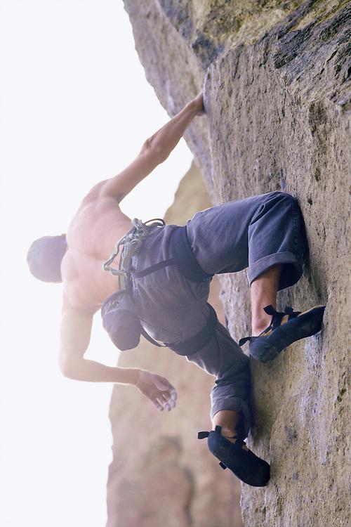Shirtless man rock climbing seen from below.