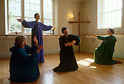 As bright sunlight fills a bare studio room, and a wooden cross is propped up in the corner, Paula Douthett (left) and three other members of the evangelical Sacred Dance Ministry (Group) perform a moment from the biblical nativity scene in her house at Milbourne St Andrew, Dorset, England. Together they are acting as part of the International Christian Dance Fellowship whose performers include performers, choreographers and teachers of all styles of dance technique, as well as those who dance in worship, intercession, healing, evangelism and prophetic interpretation. In the middle, a lady pretends to be holding the baby Jesus while the others play the roles of angels as they express wonder and admiration for this miraculous moment.