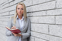 Portrait of beautiful businesswoman holding organizer while leaning on wall