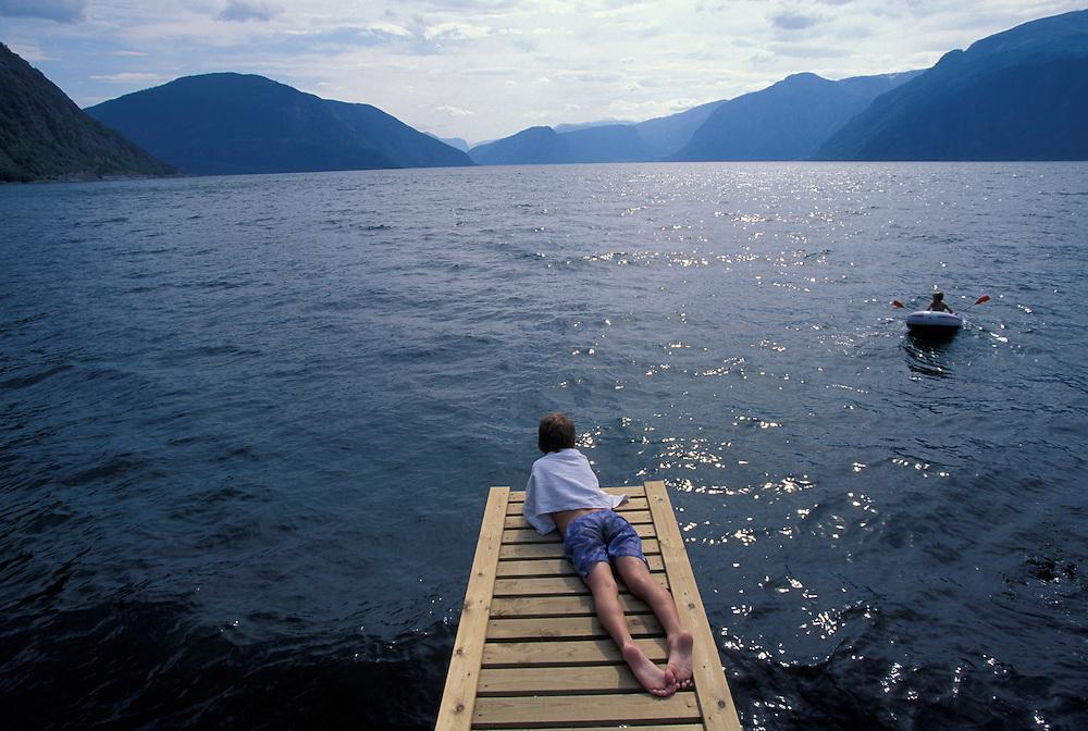 Europe, Norway. (MR) Family swims in the Sognefjord near town of Hermansverk, Norway