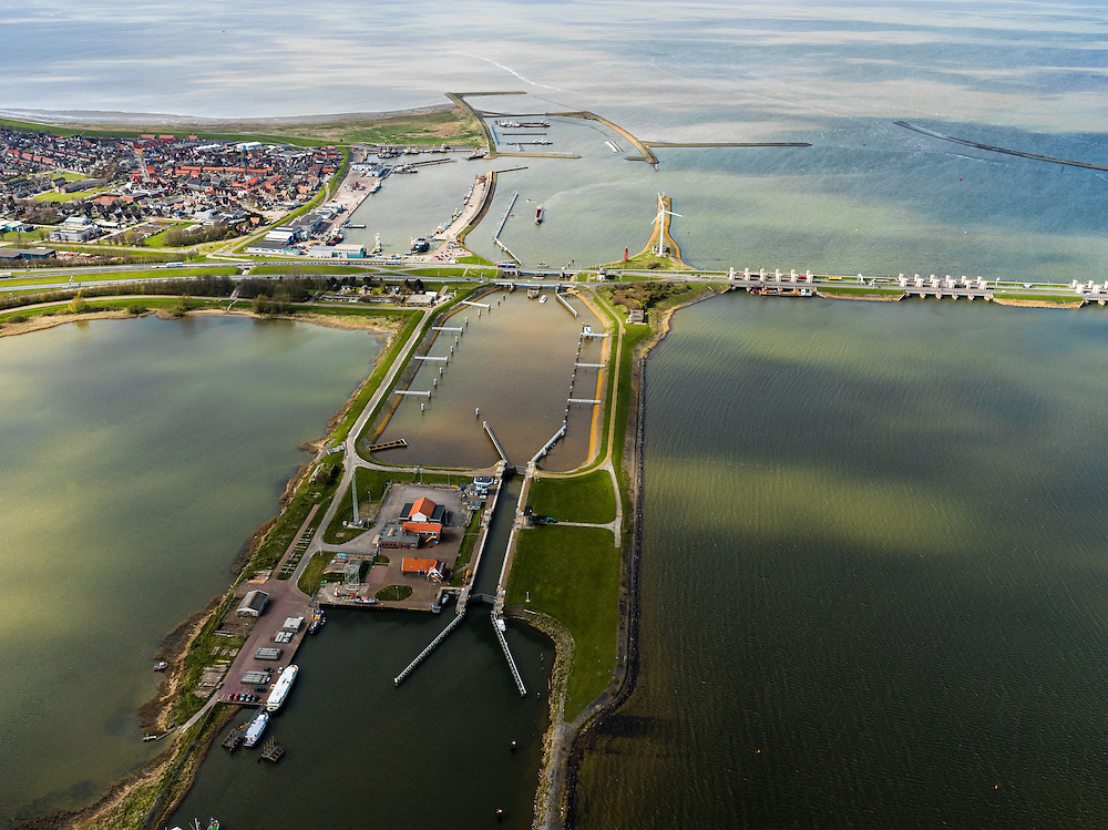 Nederland, Noord-Holland, Gemeente Wieringen, 16-04-2012; Den Oever, begin Afsluitdijk, gezien naar het noordoosten. Aan de horizon is de kust van Friesland zichtbaar. De 32 kilometer lange dijk vormt de waterkering tussen Waddenzee (links) en IJsselmeer (rechts). In de dijk de Stevinsluizen (spuisluizen of uitwateringssluizen). In de voorgrond de schutsluis voor de scheepvaart. Aanleg van de dijk vormde onderdeel Zuiderzeewerken, initiatief van ingenieur Cornelis Lely..Den Oever, beginning Enclosure Dam, looking east. The Stevin sluices sluice surplus water to the Wadden sea, in the foreground the lock for vessels. Construction of the dam was part of the Zuiderzee Works, an initiative of engineer Cornelis Lely..luchtfoto (toeslag), aerial photo (additional fee required).foto/photo Siebe Swart.luchtfoto (toeslag), aerial photo (additional fee required).foto/photo Siebe Swart