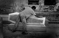 A coffin maker sands the side of his work in the capitol of Port-au-Prince