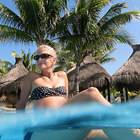 A half-underwater image of a woman relaxing in a resort pool.