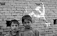 Two friends and the Maoist sick and hammer sign left on a wall.