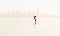 A man paddling on his stand-up paddle board on Elliott Bay with downtown Seattle in the background.