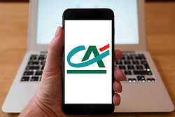 Using iPhone smartphone to display logo of Credit Agricole Bank , French network of cooperative and mutual banks comprising the 39 Crédit Agricole Regional Banks