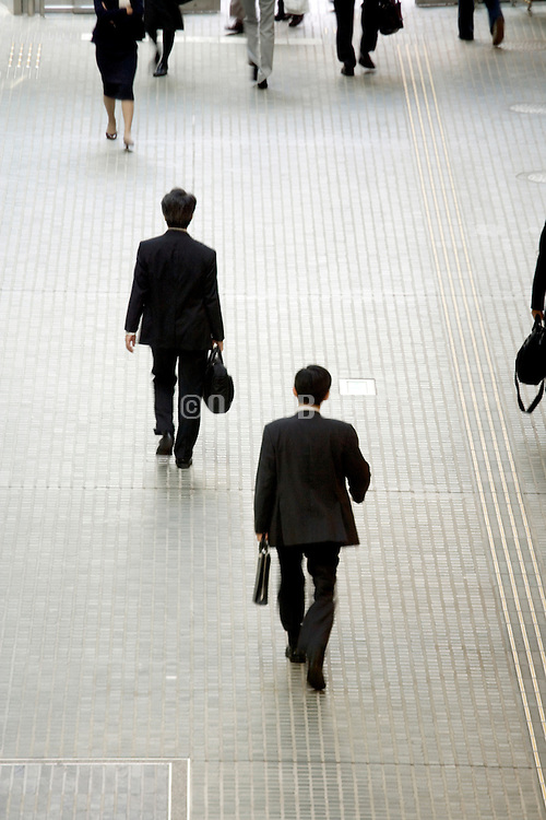 overhead view of businesspeople walking in a hallway in a large office building