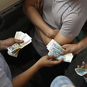 THE PHILIPPINES (Manila). 2009. Gamblers settle their debts as money changes hands during the cockfighting  at the Makati Coliseum, Makati City, Manila. Photo Tim Clayton<br /> <br /> Cockfighting, or Sabong as it is know in the Philippines is big business, a multi billion dollar industry, overshadowing Basketball as the number one sport in the country. It is estimated over 5 million Roosters will fight in the smalltime pits and full-blown arenas in a calendar year. TV stations are devoted to the sport where fights can be seen every night of the week while The Philippine economy benefits by more than $1 billion a year from breeding farms employment, selling feed and drugs and of course betting on the fights...As one of the worlds oldest spectator sports dating back 6000 years in Persia (now Iran) and first mentioned in fourth century Greek Texts. It is still practiced in many countries today, particularly in south and Central America and parts of Asia. Cockfighting is now illegal in the USA after Louisiana becoming the final state to outlaw cockfighting in August this year. This has led to an influx of American breeders into the Philippines with these breeders supplying most of the best fighting cocks, with prices for quality blood lines selling from PHP 8000 pesos (US $160) to as high as PHP 120,000 Pesos (US $2400)..