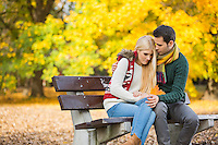 Passionate young man hugging shy woman on park bench during autumn