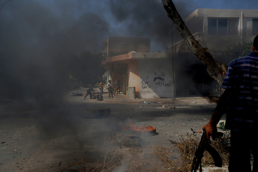 A group of rebel fighters set tires on fire to use its smoke as protection against enemy snipers in Zawiya.