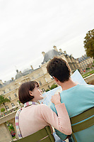 Young couple sitting on chairs looking at map in park back view