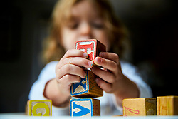 Young Girl Holding Alphabet Blocks