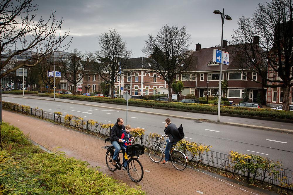 In Amersfoort fietst een vader met zijn zoontje over het fietspad terwijl hij kijkt hoe een andere man aan het bellen is tijdens het fietsen. <br /> <br /> In Amersfoort a father is cycling with his son on his bike.