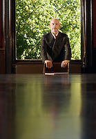 Man Standing at Head of Conference Table greenery behind