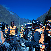 "Mountain Biking on Death Road, Bolivia...A tour group of Mountain Bikers stop to be briefed about the next stage of the journey by their tour leader...The North Yugas Road is a 64 Kilometer road leading from La Paz to Corioico. It is legendary for it's extreme danger and in 1995 the Inter American Development Bank christened is as the ""world's most dangerous road"".. The road was built in the 1930's during the Chaco War by Paraguayan prisoners to connect the Amazon rainforest region of Northern Bolivia to it's capital City La Paz. One estimate is that 200 to 300 travelers were killed yearly along the road. On 24 July 1983, a bus veered off the Yungas Road and into a canyon, killing more than 100 passengers in what is said to be Bolivia's worst road accident..A new stretch of the La Paz-Coroico highroad was opened in 2006 to bypass the notorious stretch known as death road..The danger of the road has now made it a popular tourist destination starting in the 1990's and drawing thrill-seekers and mountain bike enthusiasts who ride on the 64km mainly downhill stretch from La Cumbre, a 4,700 meter peak to Yolosa, a decent of 3600 meter's (11,800 feet). The journey includes breathtaking views of snow covered peaks and towering cliffs and starts along modern asphalted road before entering the jungle itself and the most dangerous and notorious part of the ride. The infamous narrow dirt road, most of the road no wider than 3.2 meter's, is cut into the side of the mountain with sheer drops to the left of up to 600 meter's with virtually no safety rails on the winding steep decent..There are now many tour operators catering to this activity, providing information, guides, transport and equipment. Nevertheless, the Yungas Road remains dangerous. At least 13 of these cyclists died on the ride since 1998, the latest A 28-year-old Israeli traveler was killed in April 2010  the group of cyclists arrived at a heavily foggy area. The woman got separated from the group, and fell into a"