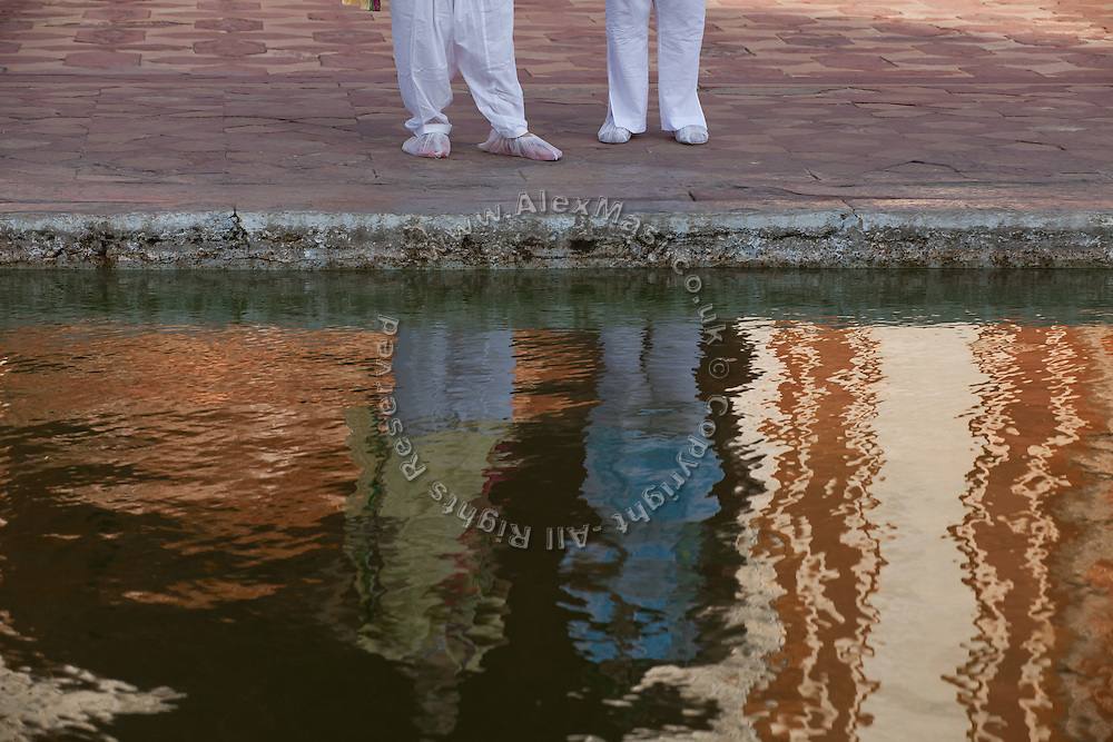 Visitors with shoe-covers for the monument's own protection, are standing in front of a pool inside the Taj Mahal complex, in Agra.