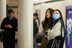 © Licensed to London News Pictures. 14/02/2020. London, UK. A commuter wearing a surgical face mask waits for a London Underground train at Temple station as there are fears that the virus could already be on the London Underground. Photo credit: Dinendra Haria/LNP