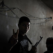 A teenage fighter gestures to the camera before head to the frontline in eastern Zawiyah.