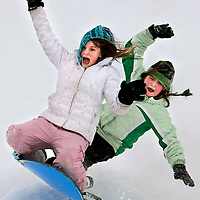 Caitlin Kopp, 11, and Alexis Ernest, 11, right, react as they fly through the air after hitting a bump while sledding in Elmwood Park after school was called off in West Fargo from the snowy weather.