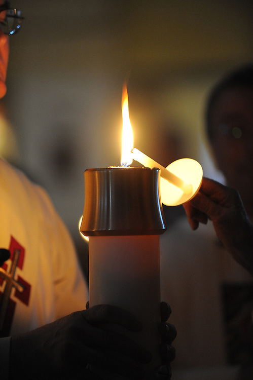 An Easter candle is used to light small candles during an Easter Vigil service. (Sam Lucero photo)