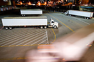 Making a sharp corner, a tractor trailer rig is blurred as several other rigs prepare to head out to the road as well.