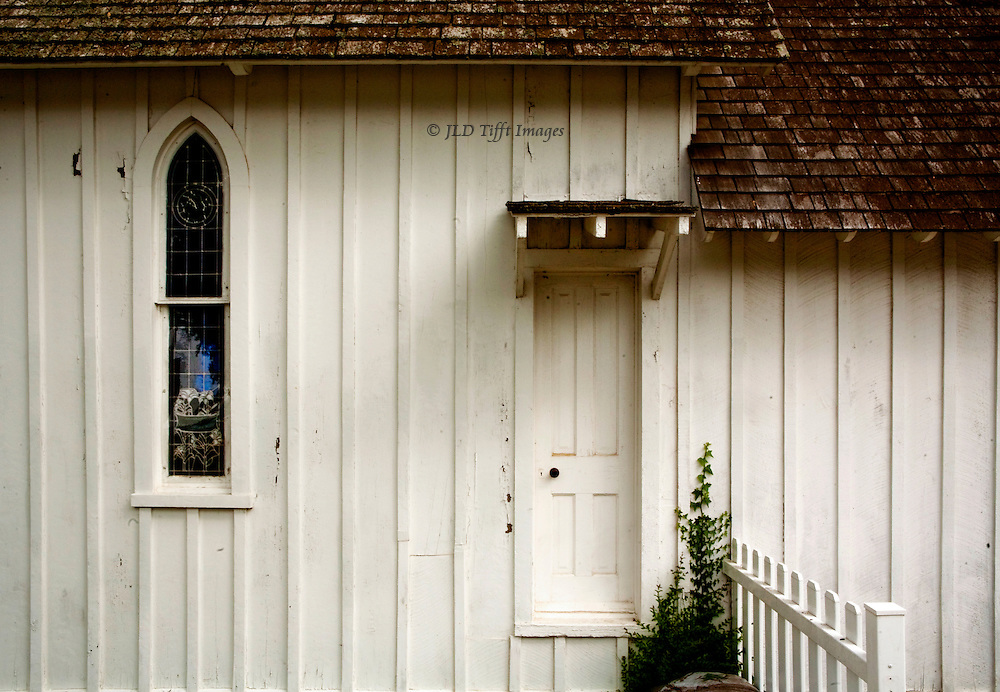 Detail side view of the tiny St. Peter's Episcopal Church, Solomon's Island, MD built 1889.  Narrow pointed arch window, narrow door (closed), section of picket fence, and wooden shingled roof.  Geometric sense of parallels and angles.