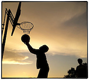 Gary Cosby Jr.  iPhone photographs<br /> Kids playing basketball at sunset.