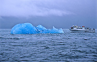 An iceberg and tour boat in Holkham Bay, Southeast Alaska.  The iceberg is larger than the tour boat.