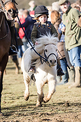© Licensed to London News Pictures. 26/12/2017. Petworth, UK. A child riding a small pony at the Chiddingfold, Leconfield and Cowdray Boxing Day hunt as they leave Petworth House to large crowds of supporters. Photo credit: Vickie Flores/LNP