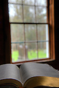 An open bible in front of a church window looking out into the adjacent cemetery.