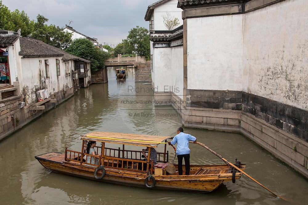 Boats and gondolas along a canal at Pingjiang Road in Suzhou, China.