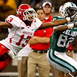 November 10, 2011; New Orleans, LA, USA; Tulane Green Wave wide receiver Xavier Rush (82) catches a ball past Houston Cougars defensive back Thomas Bates (13) during the second quarter at the Mercedes-Benz Superdome.  Mandatory Credit: Derick E. Hingle-US PRESSWIRE