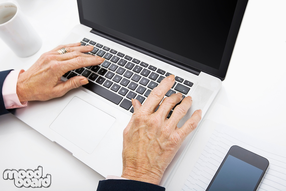 Senior businesswoman using laptop at office desk