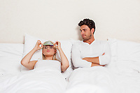 Displeased young man looking at woman wearing eye mask in bed