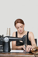 Young female tailor stitching cloth on sewing machine over colored background
