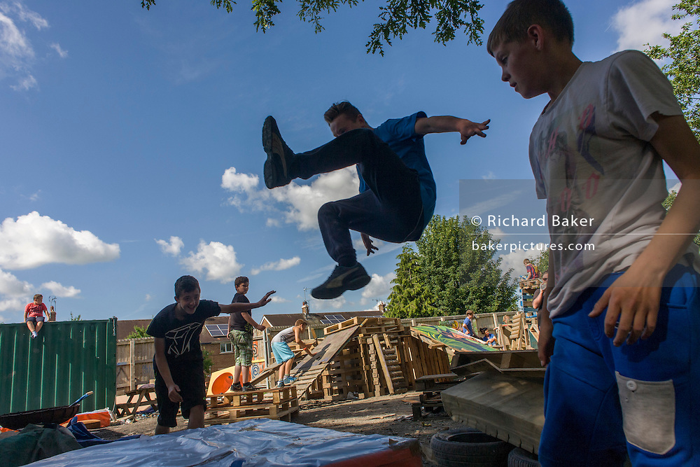 Boy somersaults onto matt in risk averse playground called The Land on Plas Madoc Estate, Ruabon, Wrexham, Wales.