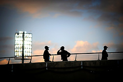 Security guards stand on the back row against a sunset and the Floodlights in the The Royal Bafokeng Stadium in Rustenburg, Phokeng, South Africa. Venue for the FIFA Confederations Cup South Africa 2009 and the FIFA World Cup South Africa 2010