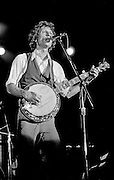 "John Hartford at the Armadillo World Headquarters in Austin Texas March 23, 1979.  Hartford (December 30, 1937? June 4, 2001) was an American folk, country and bluegrass composer and musician known for his mastery of the fiddle and banjo, as well as for his witty lyrics, unique vocal style, and extensive knowledge of Mississippi River lore. Hartford recorded several songs for the soundtrack to the movie O Brother, Where Art Thou, and won a Grammy for his performance. Hartford wrote the Glen Campbell hit, ""Gentle On My Mind,"" which is one of the most widely recorded country songs. Hartford performed with a variety of ensembles throughout his career, and is perhaps best known for his solo performances where he would interchange the guitar, banjo, and fiddle from song to song. He also invented his own shuffle tap dance move, and clogged on an amplified piece of plywood while he played and sang.  Hartford died of non-Hodgkin's Lymphoma, on June 4, 2001 in Nashville Tennessee.  The Armadillo World Headquarters was a legendary club in Austin Texas that was torn down in 1981."