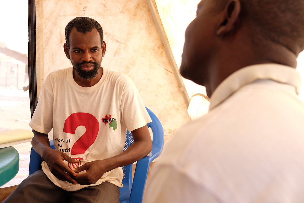 HIV activist Boubacar Alpha Diallo tells a man after testing that he is HIV negative at the MSF mobile clinic in the neighbourhood of Tombolia, Conakry, Guinea on March 18, 2016. The man in is an imam from the local mosque and explains that he has been faithful to his wife since they have been married. He is relieved when his results show he is HIV negative. Bouboucar encourages the man to ask his wife to be tested also to be completely sure they are both HIV negative. MSF launched a HIV testing campaign in Conakry with the support of health authorities moving throughout several neighbourhoods throughout 2016.<br /> <br /> Despite countries in West and Central Africa having a relatively low HIV prevalence (